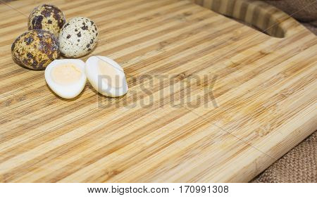 Hard boiled quail egg halves with egg shells on wooden board, photographed with natural light