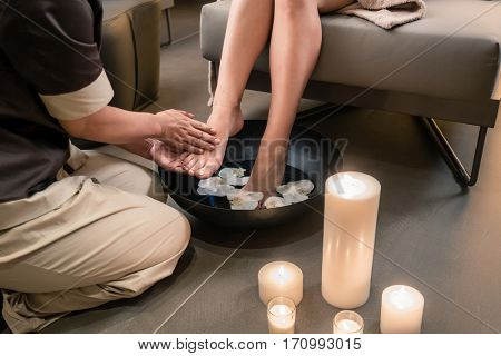 Close-up of the hands of an Asian therapist during foot washing treatment in spa and beauty center