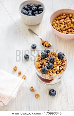 Fitness breakfast with homemade granola from yoghurt, flake and blueberries on white desk background