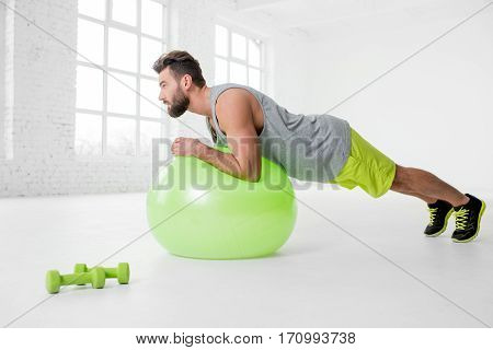 Handsome man in sportswear holding plank with fitball in the white gym interior poster