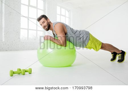 Handsome man in sportswear holding plank with fitball in the white gym interior