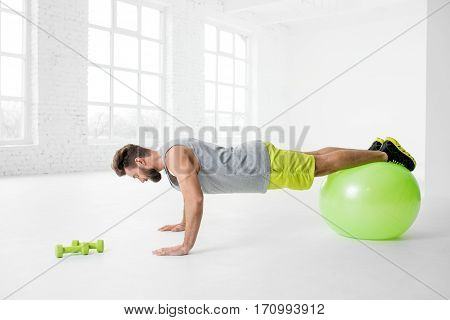 Handsome man in sportswear making pushups with fitball in the white gym interior