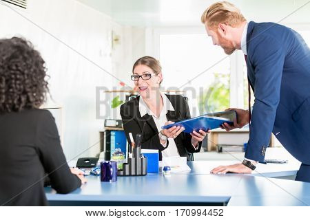 Man hands over a blue ring binder to his co-worker at the office