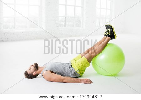 Handsome man exercising with fitball in the white gym interior