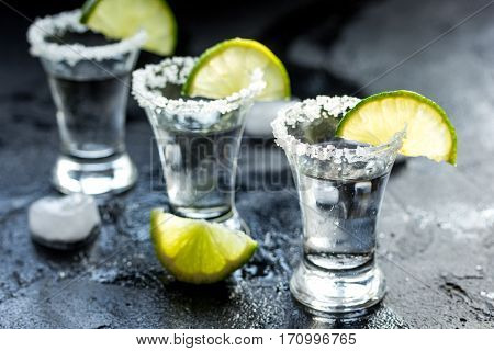 Alcohol shots with fresh green lime slices and salt on black table background