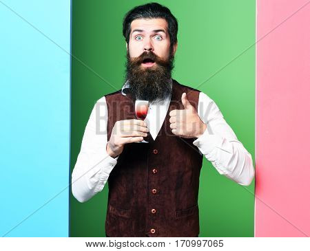 handsome bearded man with long beard and mustache has stylish hair on surprised face holding glass of alcoholic shot in vintage suede leather waistcoat on colorful studio background copy space