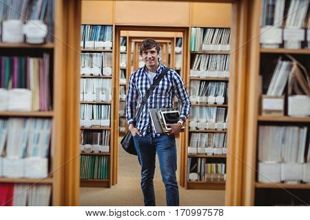 Portrait of student standing in library with laptop and digital tablet at college