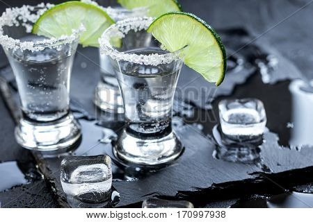 Silver tequila shots with ice cubes and fresh lime slices on black table background