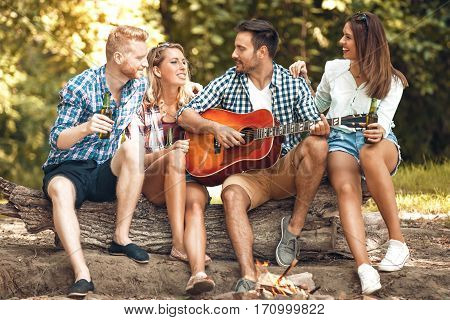 Fiends enjoying camping and playing guitar. Spring time.