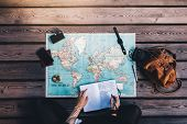 Young woman making notes in diary looking at the world map with travel accessories around. Tourist planning vacation using a world map. poster