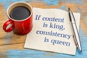 If content is king, consistency is queen - blogging and social media tip - handwriting on a napkin with a cup of coffee poster