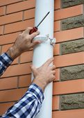 Contractor installing and repair pvc rain gutter system pipeline. Guttering Plastic Guttering & Drainage by Handyman hands. poster