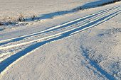 snow-covered road after the last snowfall. Roadway small size which traces the track and the wheels. Photo close-up in winter. Small depth of field poster