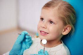 Cute smiling girl visiting dentist. Doctor's hands with dental tools examining child's teeth.