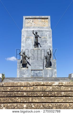 Historical Monuments. Stone Monument Of The Greek Revolutionary Heroes Of 1821 Against The Blue Sky,
