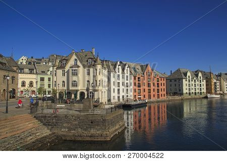 Norwegian town of Alesund in summer. Beautiful places in Scandinavia. View of Alesundet Canal from Apotekertorget, colored houses, pier, boat poster