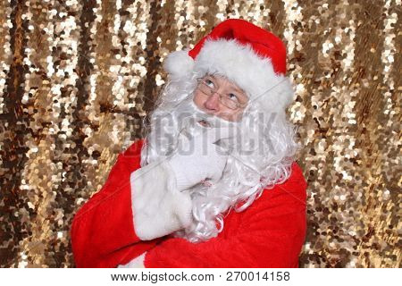 Santa Claus. Santa Claus holds his fingers to his face and he is deep in thought. Santa Thinking. gold sequin background. Christmas holiday images.