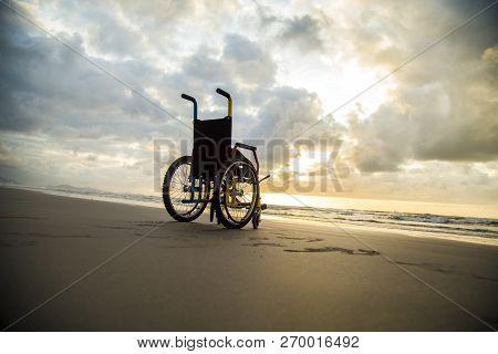 sunset childlike wheelchair horizon sand beach sky poster