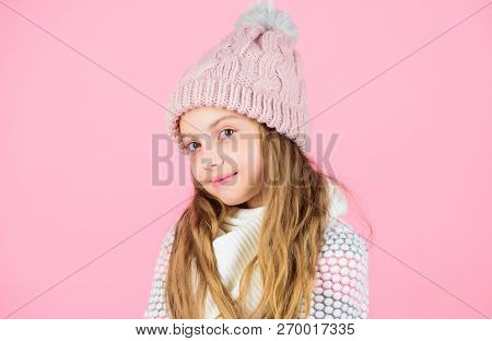 Child Long Hair Warm Soft Woolen Hat Enjoy Softness. Kid Girl Wear Knitted Soft Hat Pink Background.