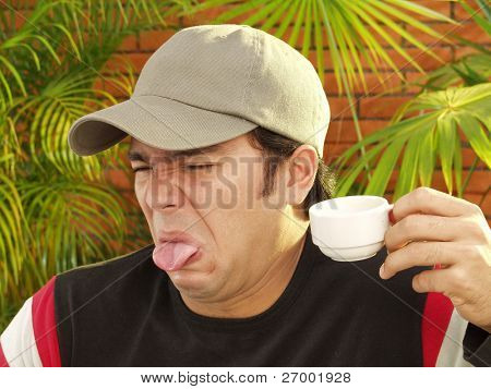 Expressive young man portrait drinking coffee.