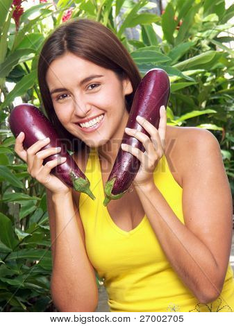 Young woman holding a fresh eggplant on a garden.