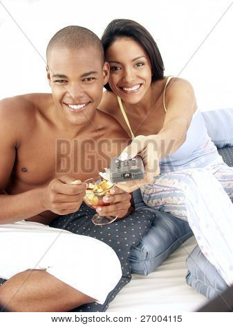 Young hispanic couple enjoying and eating fruit salad on bed. Young hispanic woman holding a remote control. Young couple sharing and watching television.