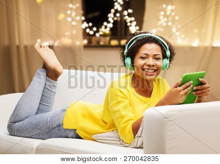 technology, christmas and people concept - happy african american young woman lying on sofa with tablet pc computer and headphones listening to music at home over garland lights background