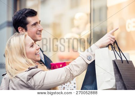 Happy couple at shop window doing Christmas shopping