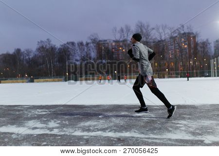Photo of man in black sports clothes running in winter park