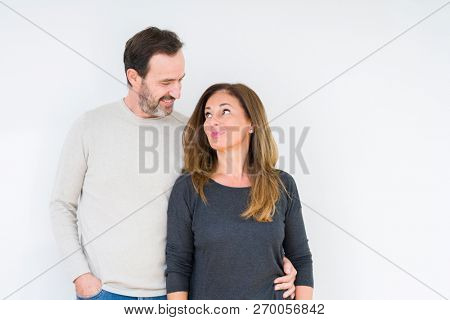 Beautiful middle age couple in love over isolated background smiling looking side and staring away thinking.