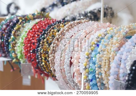 Costume jewelry headbands, handmade accessories made of stones, beads and rhinestones. Beautiful multi-colored jewelry on store boutique shop shelves, Treasure tiara with stones for female poster