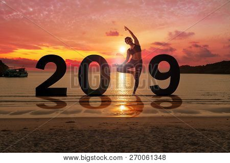 Greeting Card 2019 Happy New Years. Silhouette Of Healthy Young Woman Practicing Yoga On Tropical Be