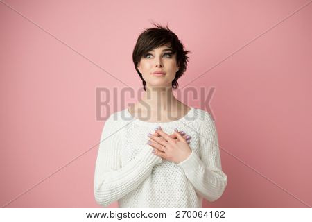 Young pretty woman  smiling and looking up to the top left corner with hands on chest. Happy smiling woman feels grateful, hopes for successful plan realization, believes in success