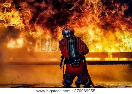 Firefighter Training., Fireman Using Water And Extinguisher To Fighting With Fire Flame In An Emerge