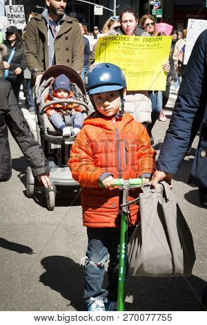 March For Our Lives: A boy on a scooter and toddler in a stroller among adults at the national march to end gun violence, 6th Ave NEW YORK MAR 24 2018.