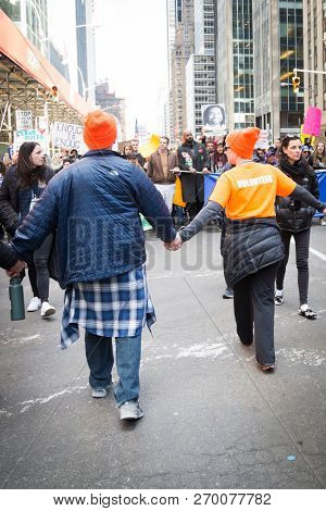 March For Our Lives: Governor Andrew Cuomo surrounded by volunteers holding hands while walking in the march on 6th Ave to end gun violence, NEW YORK MAR 24 2018.
