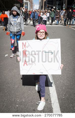 March For Our Lives: A young girl holds a sign with the initials NRA spelling out Not Responsible Adults during the national march to end gun violence, 6th Ave NEW YORK MAR 24 2018.