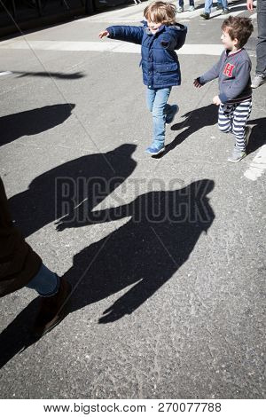 March For Our Lives: Two little boys have fun chasing shadows of adults ahead of them during the national march to end gun violence, 6th Ave NEW YORK MAR 24 2018.