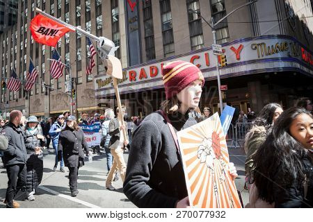 March For Our Lives: A protester passing Radio City Music Hall holds a sign in the shape of a gun with a red flag that says BAN at the march on 6th Ave to end gun violence, NEW YORK MAR 24 2018.