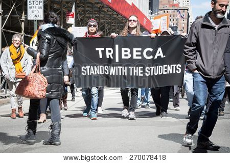 March For Our Lives: Protesters hold a banner from the Lower Manhattan neighborhood that says Tribeca Stands With The Students at the march on 6th Ave to end gun violence, NEW YORK MAR 24 2018.