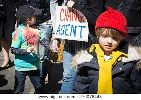 March For Our Lives: Two little boys walk with an adult holding a sign that says Change Agent at the national march to end gun violence, 6th Ave NEW YORK MAR 24 2018.