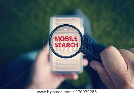 Top-down View Of A Sitting Man With The Magnifying Glass With Written Red Words Mobile Search Above
