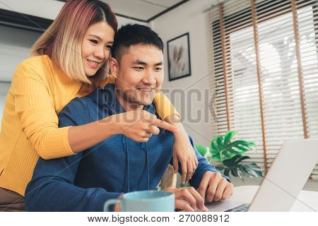 Young Asian Couple Managing Finances, Reviewing Their Bank Accounts Using Laptop Computer And Calcul