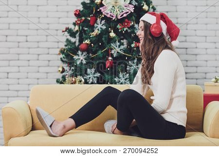 Young Couple In Red Hat Sitting On Sofa Between Christmas Trees And Listening To Music With Headphon