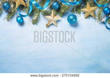 Christmas Background. Snow Fir Tree Branch, Blue Balls And Gold Star On Blue Background. Top View Wi