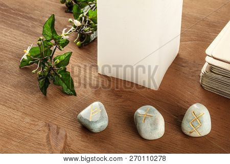 A closeup photo of Norse runes from the Futhark alphabet, stones with symbols used in Wicca and other magic and for divination, with a candle and Tarot cards on a dark rustic background with copy space poster
