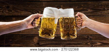 Hands Holding Mugs Of Bavarian Beer Oktoberfest.