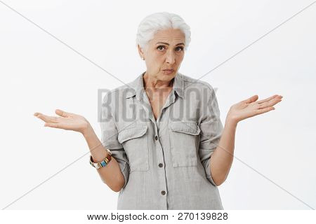 Waist-up Shot Of Clueless Unsure Cute Granny With White Hair Shrugging With Hands Spread Aside Being