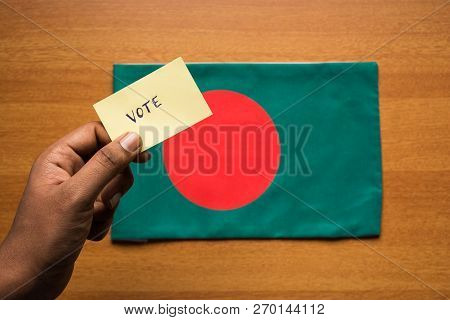 Voting Concept - Person Holding Hand Written Voting Sticker On Bangladesh Flag.