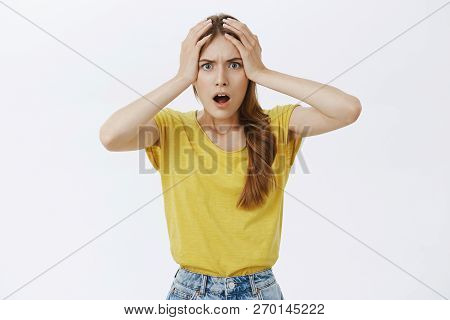 Girl having huge disaster on work feeling anxious and displeased holding hands on head in hopeless gesture opening mouth from surprise frowning standing dissatisfied and troubled over grey wall poster